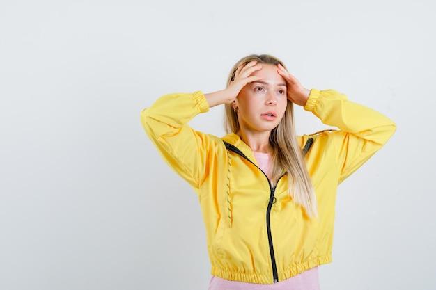 Rapariga loira com jaqueta amarela esfregando a testa e parecendo pensativa
