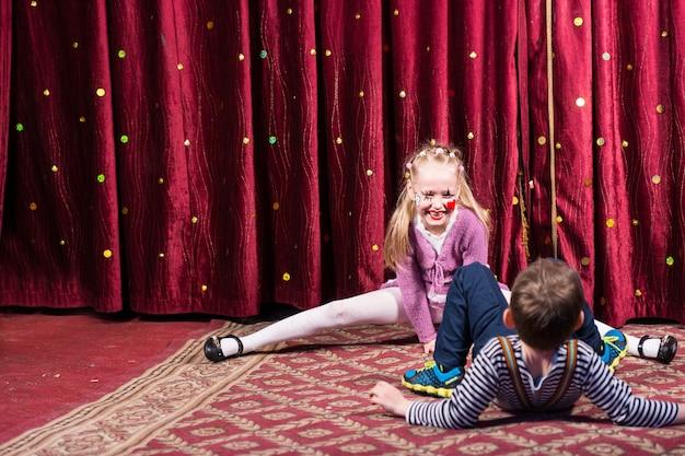 Rapariga loira com maquiagem de palhaço fazendo fendas no palco com a cortina vermelha com o menino em primeiro plano