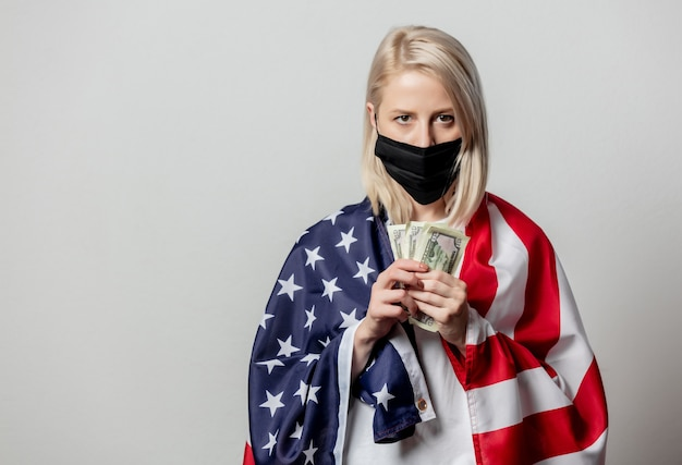 Rapariga loira com máscara facial com bandeira dos eua e dinheiro