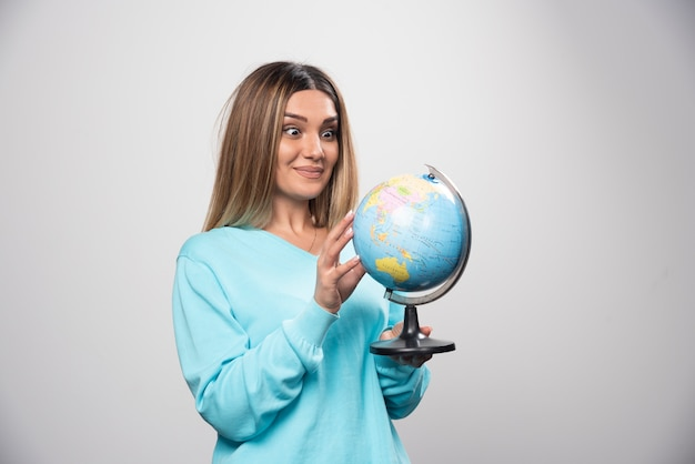 Rapariga loira com moletom azul segurando um globo, adivinhando a localização e se divertindo.