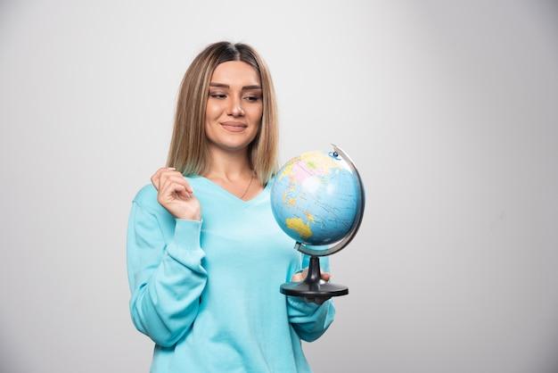 Rapariga loira com moletom azul segurando um globo, adivinhando a localização e se divertindo
