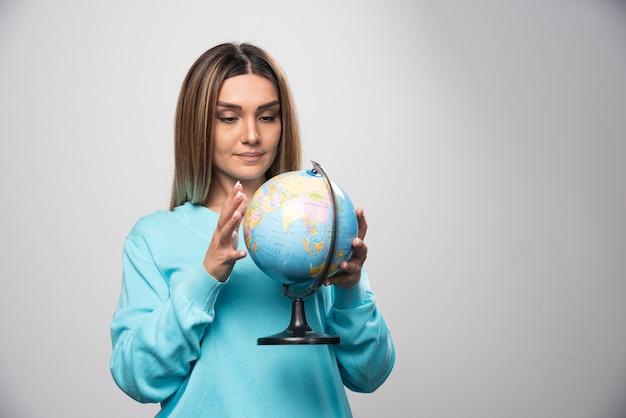 Rapariga loira com moletom azul segurando um globo e verificando o mapa da terra com atenção.