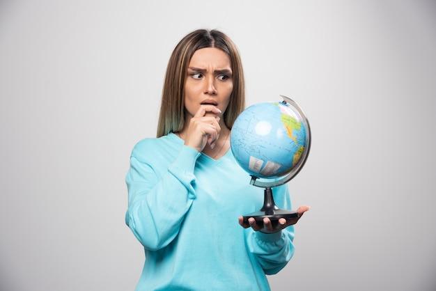 Rapariga loira com moletom azul segurando um globo, pensando com cuidado e tentando se lembrar