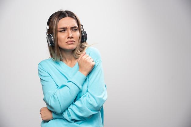 Rapariga loira com moletom azul usando fones de ouvido e tentando entender a música