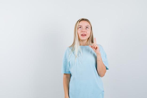 Rapariga loira com t-shirt azul apontando para cima com o dedo indicador, olhando para cima e olhando focada, vista frontal.