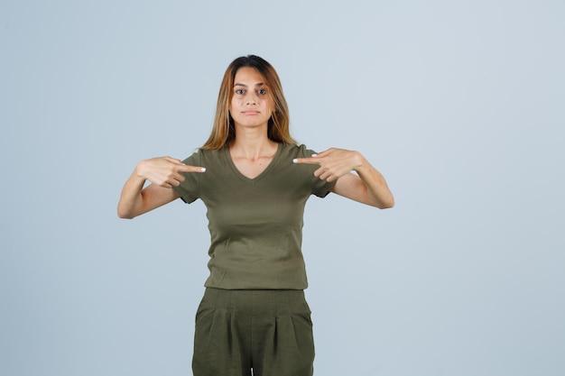 Rapariga loira com t-shirt verde azeitona e calças, apontando-se com os dedos indicadores e parecendo encantadora, vista frontal.