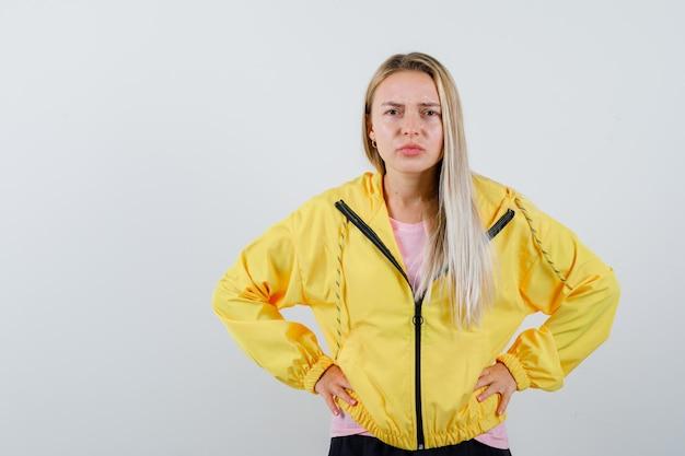 Rapariga loira com uma jaqueta amarela de mãos dadas na cintura e parecendo confusa