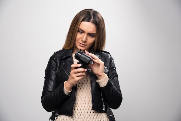 Rapariga loira com uma jaqueta de couro preta checando sua história fotográfica na dslr e parece insatisfeita