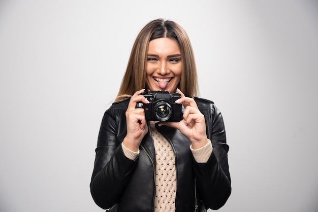 Rapariga loira com uma jaqueta de couro preta tirando selfies com uma câmera