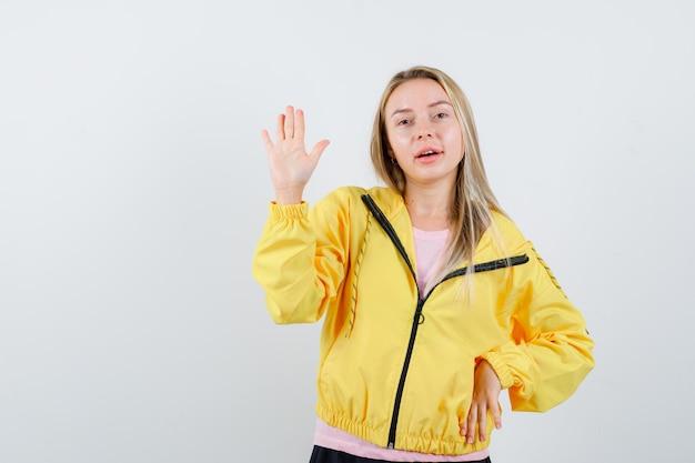 Rapariga loira com uma t-shirt rosa e uma jaqueta amarela mostrando a placa de pare e parecendo séria