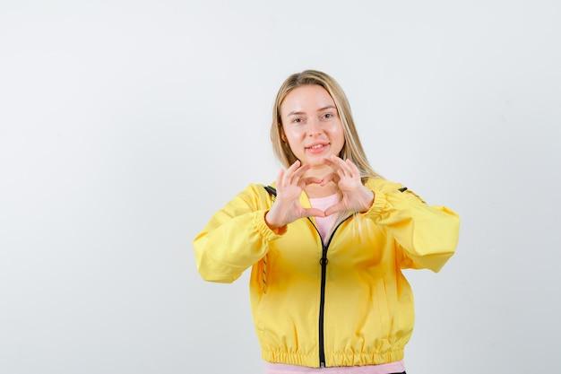 Rapariga loira com uma t-shirt rosa e uma jaqueta amarela, mostrando um gesto de amor com as mãos e parecendo atraente