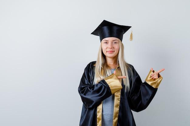 Rapariga loira com vestido de formatura e boné apontando para a direita com o dedo indicador e parecendo uma fofa