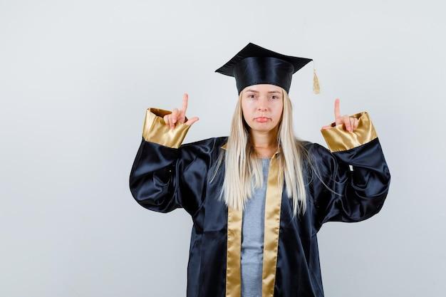 Rapariga loira com vestido de formatura e boné apontando para cima com os dedos indicadores e parecendo uma fofa