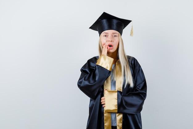 Rapariga loira com vestido de formatura e boné, colocando uma das mãos perto da boca e segurando a outra mão na barriga