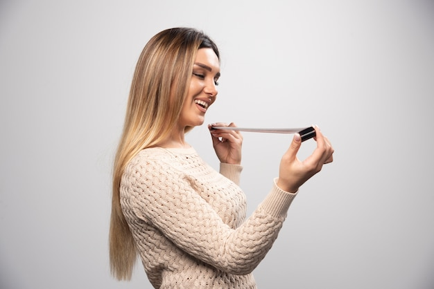 Rapariga loira conferindo as fotos no rolo de fotos e se sente feliz e positiva com o resultado.