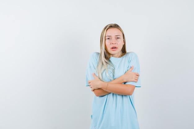 Rapariga loira de braços cruzados em t-shirt azul e olhando séria, vista frontal.