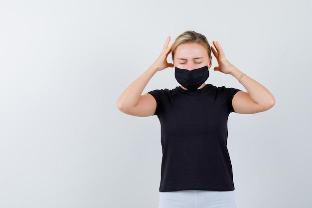 Rapariga loira de mãos dadas perto da cabeça em uma camiseta preta, calça branca isolada