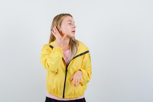Rapariga loira de mãos dadas perto da orelha para ouvir algo em uma camiseta rosa e jaqueta amarela e olhando focada