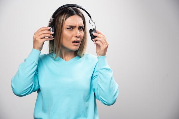 Rapariga loira de moletom azul ouve os fones de ouvido e não gosta da música.