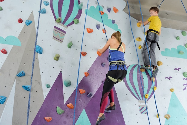 Rapariga loira e estudante agarrando-se a pequenas pedras em equipamento de escalada enquanto treinava em um centro de lazer ativo