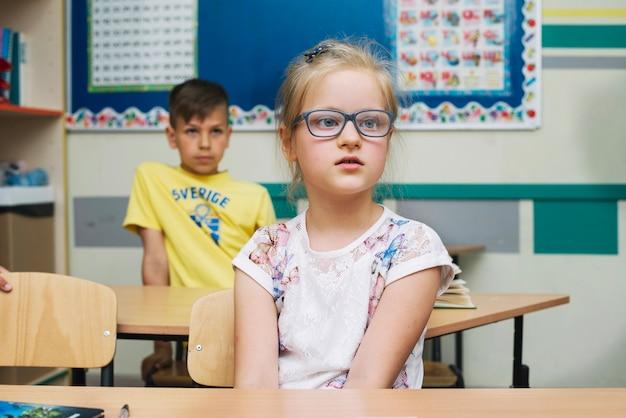 Rapariga loira em óculos sentados na mesa