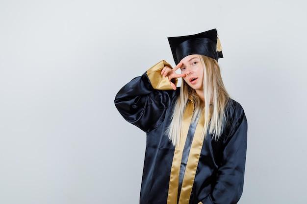 Rapariga loira em pé, mostrando o sinal v no olho e posando para a câmera no vestido de formatura e boné e olhando bonito.