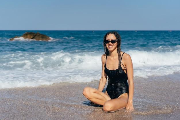 Rapariga loira em traje de banho sentado no bronzeamento de praia do mar