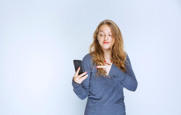 Rapariga loira enviando mensagens de texto e enviando mensagens com seu smartphone.
