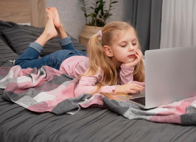 Rapariga loira estudando em casa online com um laptop na cama