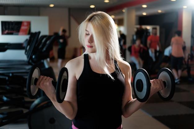 Rapariga loira fazendo exercício com halteres no ginásio