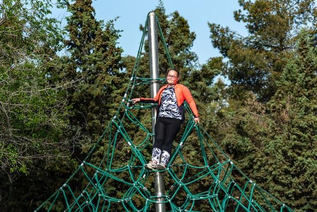 Rapariga loira gordinha com óculos subiu no topo de uma corda de pirâmide de playground.