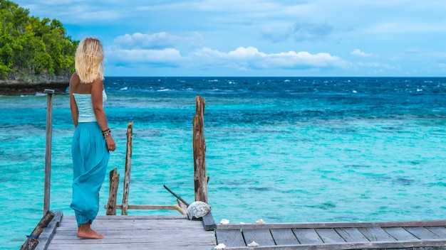 Rapariga loira hospedada no cais de madeira de uma casa de família olhando para o oceano azul, ilha gam, papuã ocidental, raja ampat, indonésia
