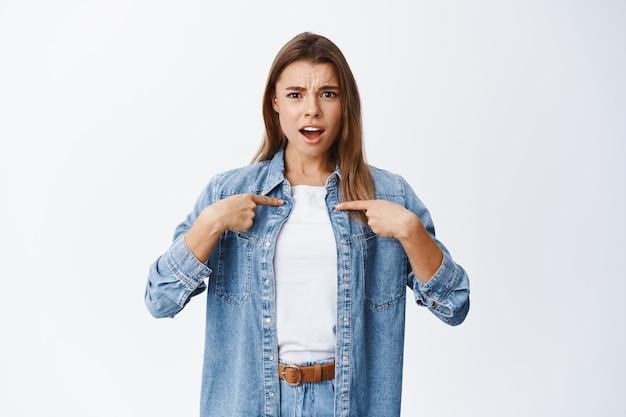 Rapariga loira insultada sendo ofendida, apontando para si mesma e franzindo a testa descontente, sendo acusada, encostada em uma parede branca
