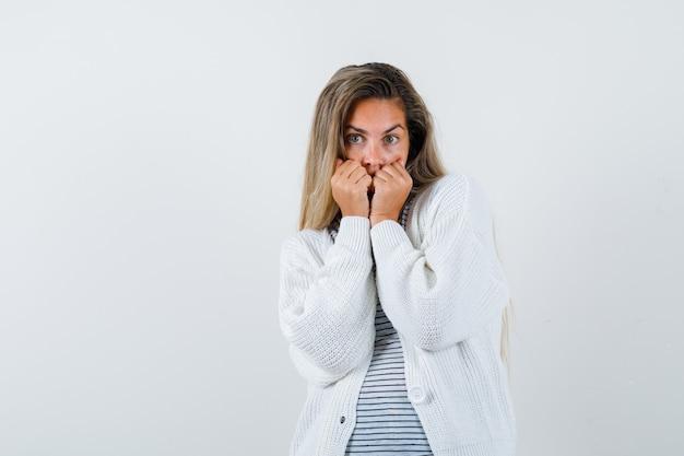 Rapariga loira mordendo os punhos emocionalmente em uma camiseta listrada, cardigã branco e calça jeans e parecendo tímida. vista frontal.