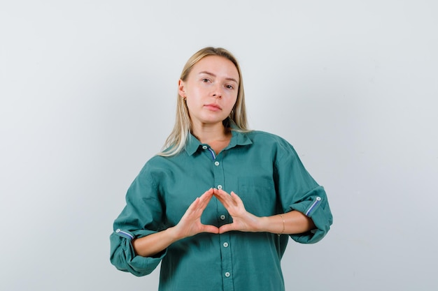 Rapariga loira mostrando gesto de seguro com uma blusa verde e parecendo radiante