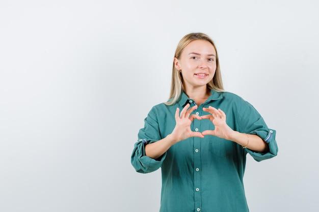 Rapariga loira mostrando um gesto de amor com as mãos na blusa verde e parecendo encantadora