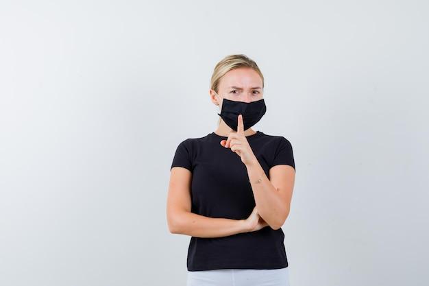 Rapariga loira mostrando um gesto de aviso enquanto mantém a mão isolada