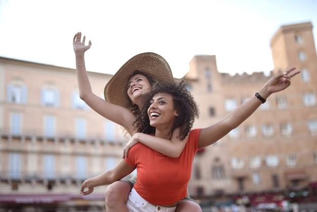 Rapariga loira nas costas de uma senhora de cabelo preto atrás de edifícios, mostrando felicidade e entusiasmo