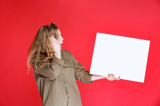 Rapariga loira olhando para uma tela e fica surpresa.