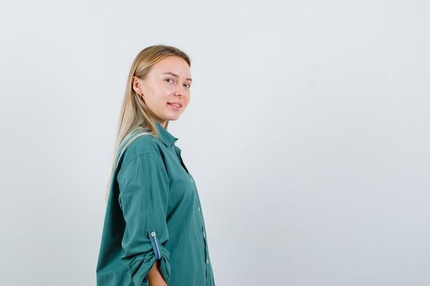 Rapariga loira olhando por cima do ombro com uma blusa verde e parecendo encantadora