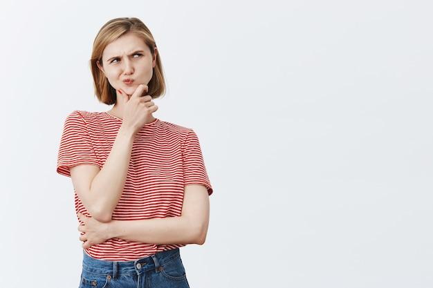 Rapariga loira pensativa complicada parecendo pensativa no canto superior direito, fazendo uma escolha