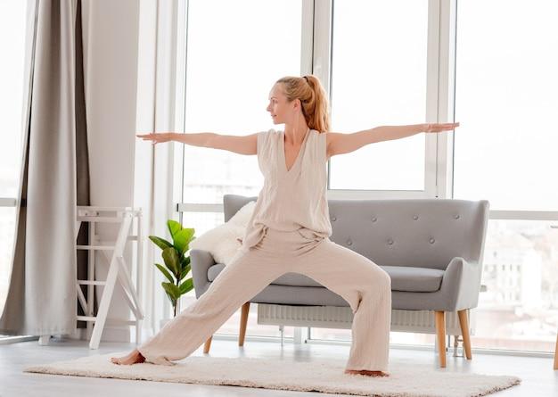 Rapariga loira praticando ioga em casa. treino de alongamento na sala com luz do sol