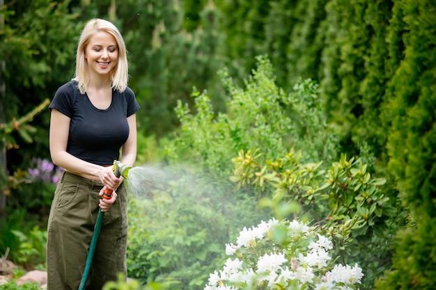Rapariga loira regando o jardim no verão