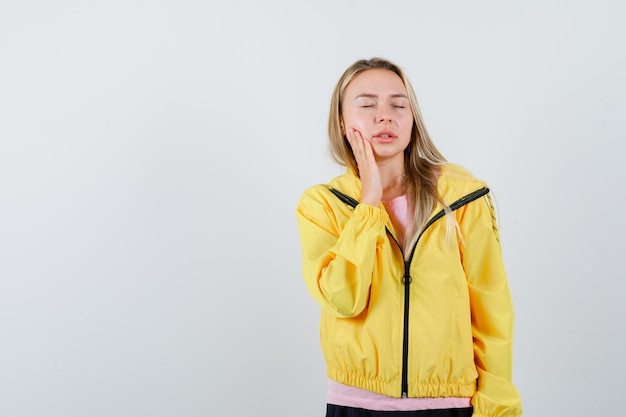 Rapariga loira segurando a mão perto da boca, tendo dor de dente em uma camiseta rosa e jaqueta amarela e parecendo exausta