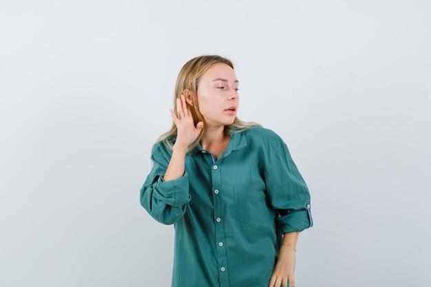 Rapariga loira segurando a mão perto da orelha para ouvir algo em uma blusa verde e parecendo focada