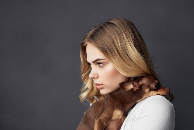 Rapariga loira segurando um pequeno cão de raça pura estúdio moda