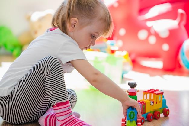 Rapariga loira sentada no chão jogando