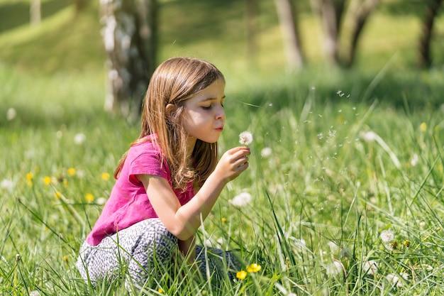 Rapariga loira soprando flores dente de leão soprando em um campo verde cheio de flores