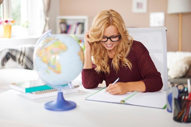 Rapariga loira sorridente a estudar em casa