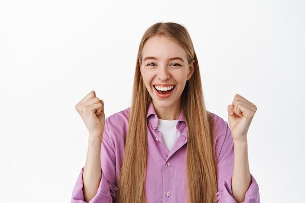 Rapariga loira sorridente comemora o sucesso, atinge o objetivo, diz sim e levanta os punhos de alegria, triunfando, em pé sobre a parede branca